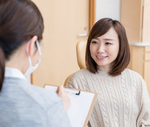 A female patient talking with her dentist about cosmetic bonding in Carrollton, TX
