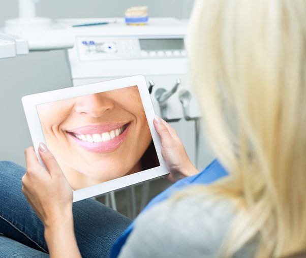 Woman looking at virtual smile design on tablet computer
