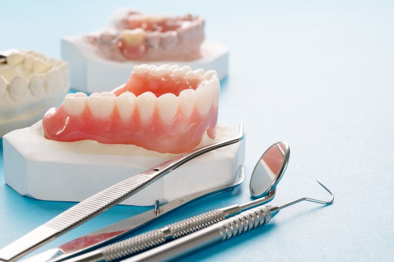 Dentures in Carrollton resting on a mouth mold with several dental instruments nearby